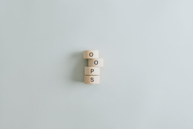 Упс знак написан на сложенных деревянных кругах на сером