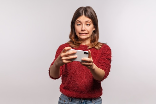 Oops, sorry! frustrated woman looking at smartphone with excuse grimace, feeling helpless