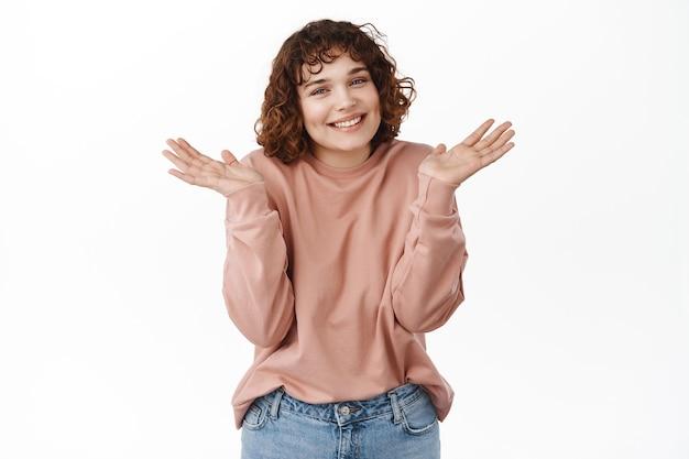 죄송합니다. 웃고 있는 수줍은 소녀는 어깨를 으쓱하고 사과하고, 아무것도 모르고, 흰색으로 질문을 받았습니다.