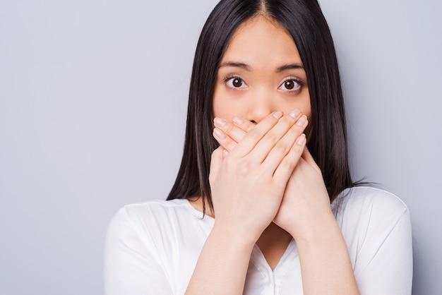 おっとっと!手で口を覆い、灰色の背景に立っている間カメラを見つめて驚いた若いアジアの女性