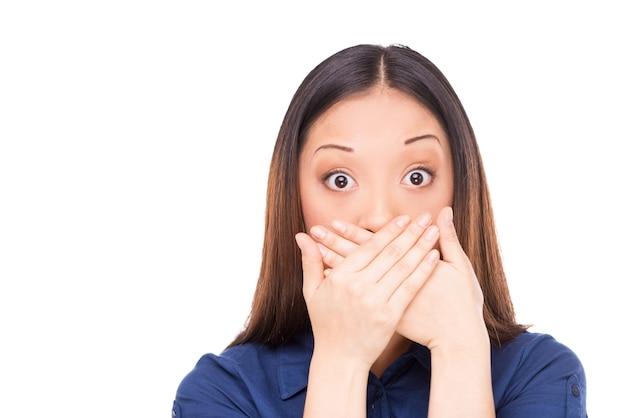 おっとっと!手で口を覆い、カメラを見つめて驚いた若いアジアの女性
