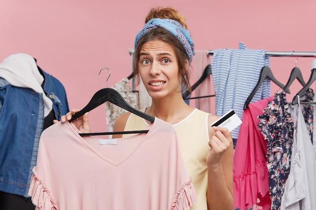 Oops! preoccupato donna con abito in boutique in una mano e carta di credito nell'altra, sentendosi perplesso che non ha soldi sul suo conto per aver pagato il suo acquisto. distese impreviste sui vestiti