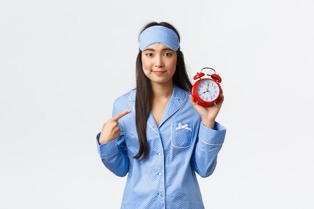 Упс, неуклюжая глупая девушка в синей пижаме и спящей маске, указывая пальцем на будильник и улыбаясь, виновато, что проспала или забыла его настроить, стоя на белом фоне, извини.