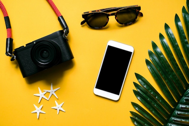 Op view camera,smartphone,sunglasses,starfish and palm leaf on yellow