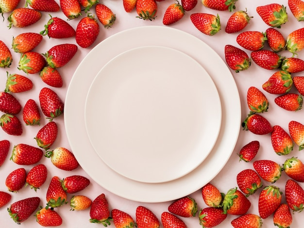 Op view of two ceramic plates surrounded with pile of ripe strawberries