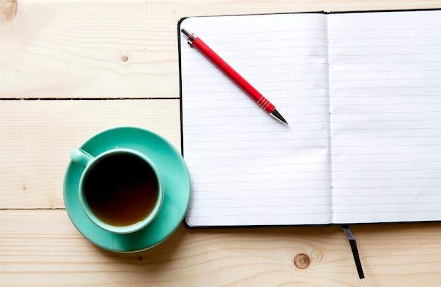 机の上の空白の白いノートブック、ペン、お茶を開く