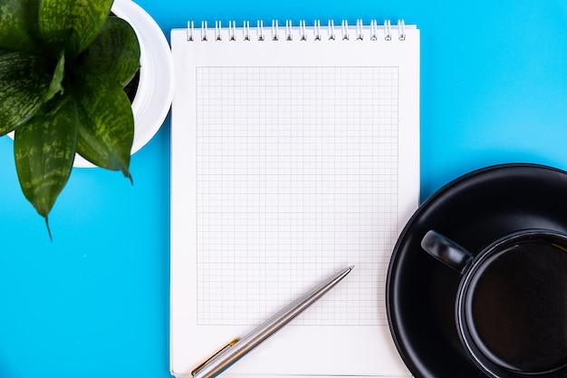 青いテーブルの上にペン、花、コーヒーのカップで、空白の白いノートを開きます。ビジネスコンセプト
