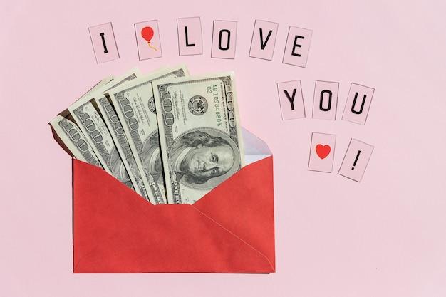 ピンクの表面で隔離された百ドル札で紙の封筒を開きます。プレゼントとして封筒に折りたたまれた紙幣。送金または節約、汚職の概念。贈り物の現金請求書