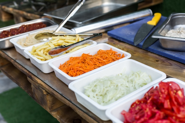 Open air kitchen products for cooking falafel in dishes on a wooden table. street food