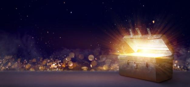 ボケ味の背景に光を放射した古代の宝箱を開く