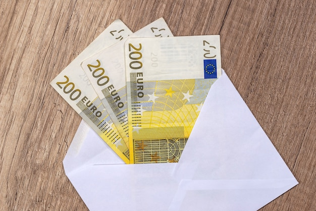 テーブルの上にユーロ紙幣の入った封筒を開きます