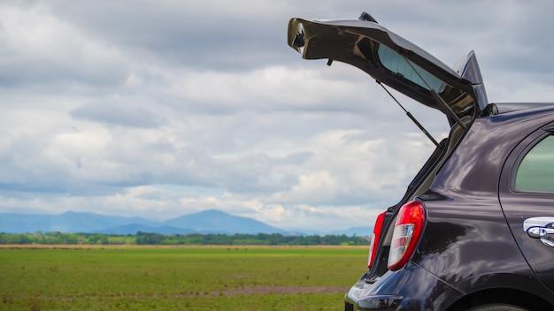 Open back door hatchback car with meadow