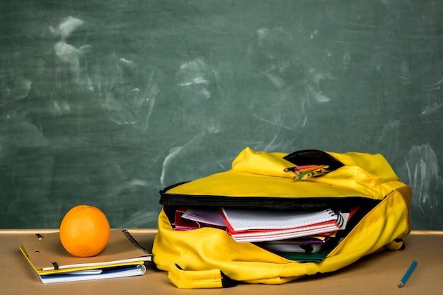 Открытый рюкзак и апельсин на столе