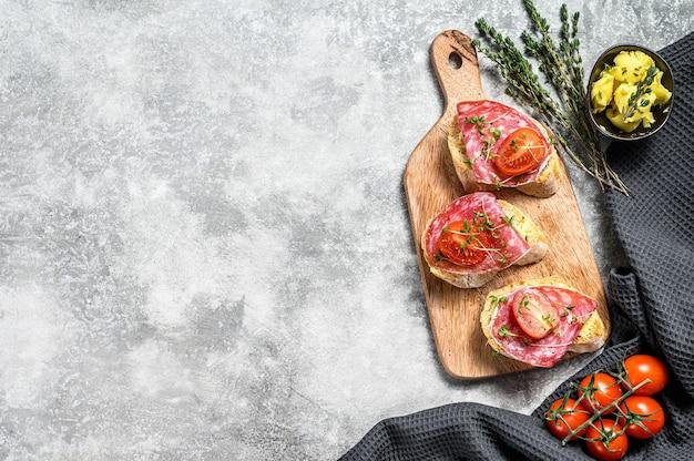 サラミサルチチョン、チェリートマト、マイクログリーンのバゲットサンドイッチを開きます。灰色の背景