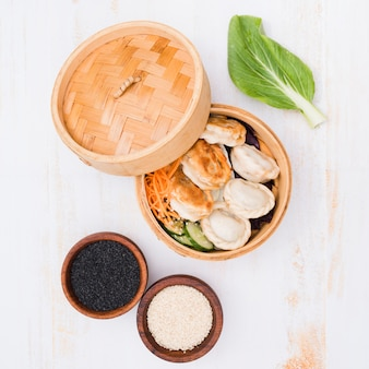An open bamboo steamers with dumplings and sesame seeds on textured backdrop