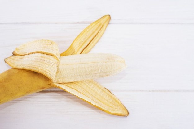 Open banana on a white wooden background. close-up.