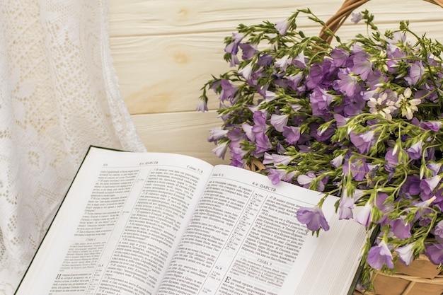 고리 버들 바구니에 성경과 꽃다발 아마를 엽니 다. 레트로 스타일, 빈티지
