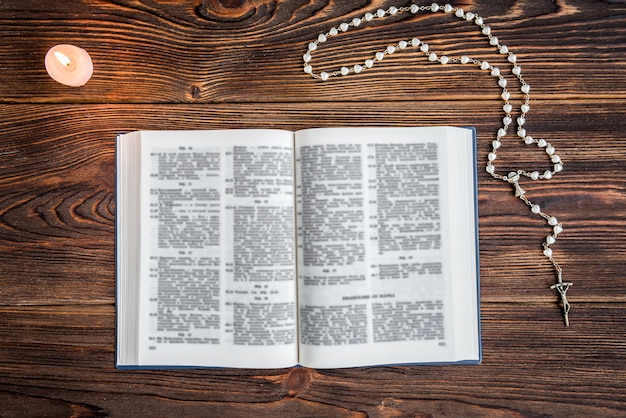 Open bible, candle, christian cross and human hands on wooden