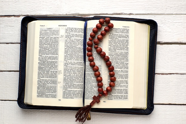 Open bible and rosary on a white wooden table