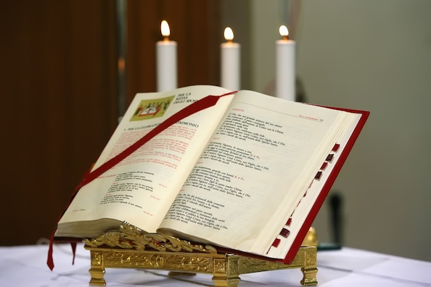 An open bible and three candles behind it