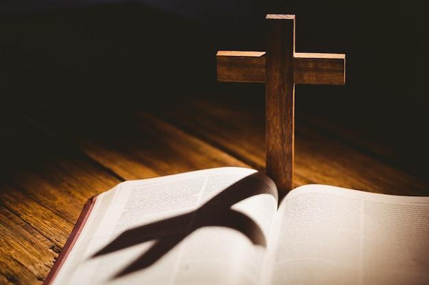 Открытая библия с иконкой распятия позади