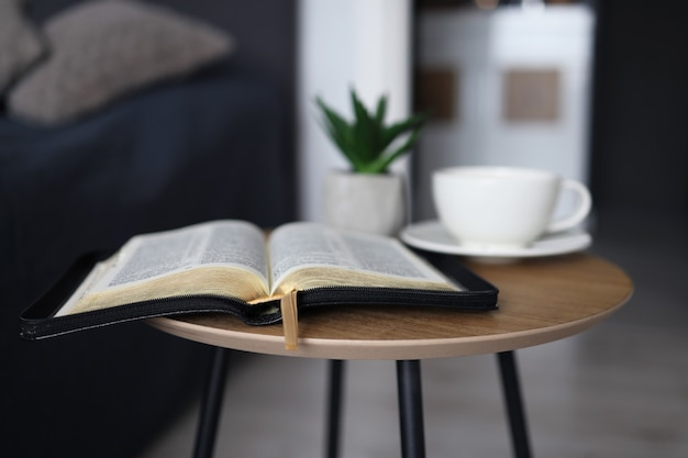Open bible with a cup of tea on a wooden table in the bedroom. time for prayer.