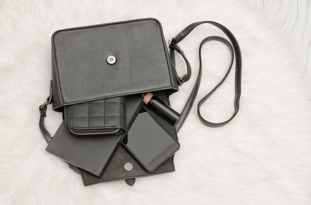 Open black bag with dropped things, notebook, mobile phone, purse. the white fur on background, top view. fashion concept