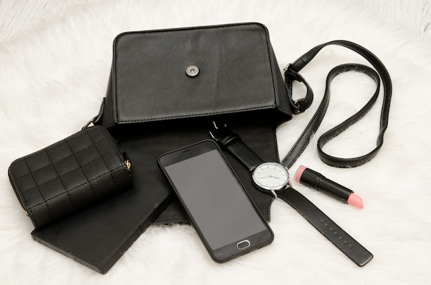 Open black bag with dropped things, notebook, mobile phone, watch, purse and lipstick. the white fur on background, top view