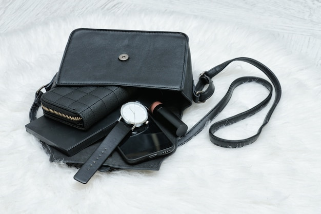 Open black bag with dropped things, notebook, mobile phone, watch and purse
