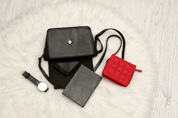 Open black bag with dropped things, notebook, mobile phone, watch and red purse.