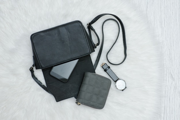 Open black bag with mobile phone, watch and purse