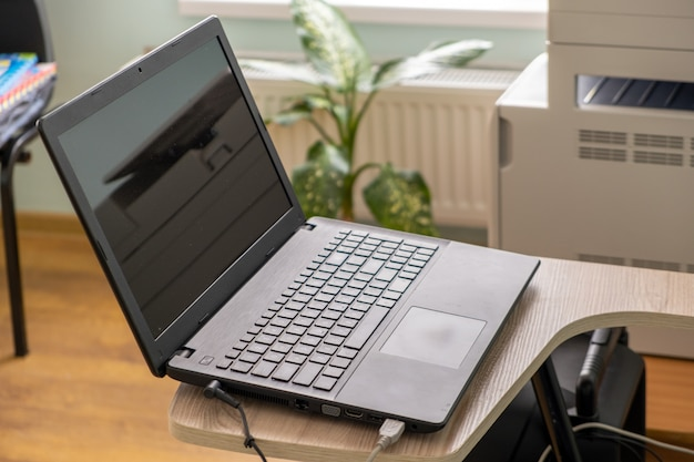 Open black laptop computer on a small chair table in office interior.