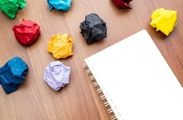 Open blank book with group of colorful crumpled paper ball on table