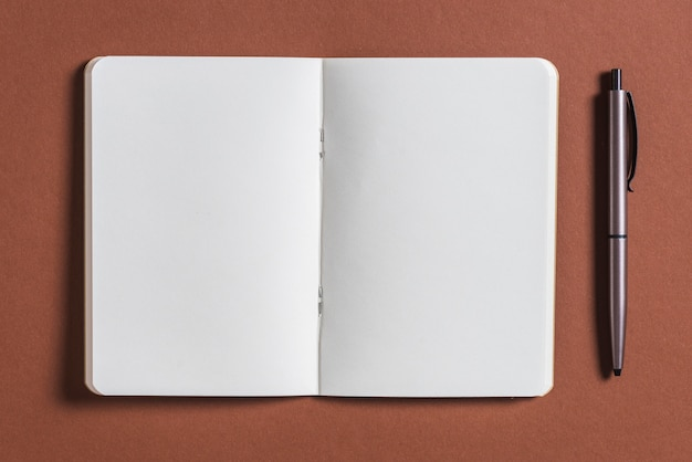 Open blank book with pen on brown background