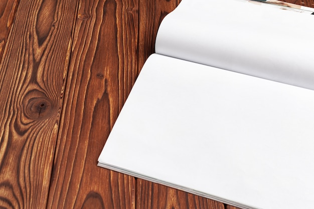 Open blank journal pages for your design copy space on wooden background