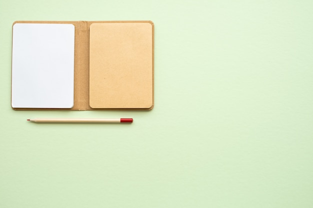 Open blank new eco notepad and pensil on light green background, copy space, top view