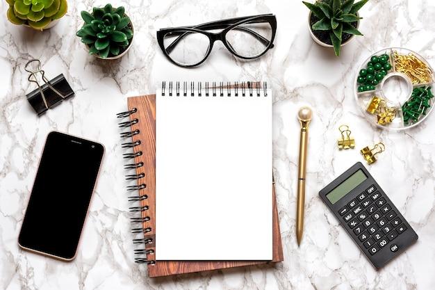 空白のノートブック、グラス、ペン、スマートフォン、多肉植物を大理石のテーブルで開く上面図フラットレイ