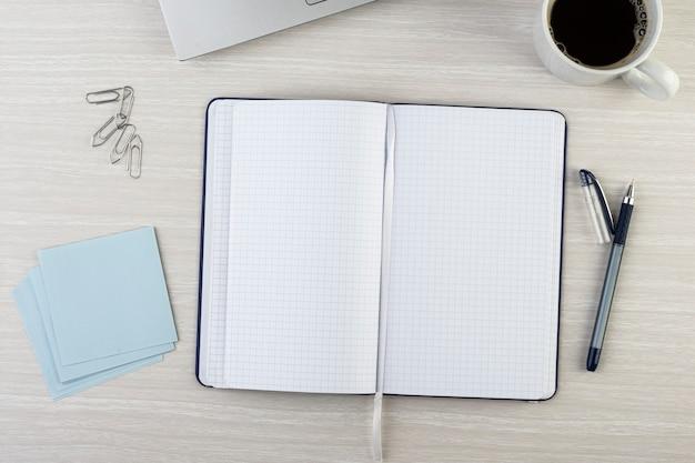 Откройте пустую записную книжку с ручкой, кофейной кружкой, скрепками и блокнотом над деревянным столом. вид сверху.