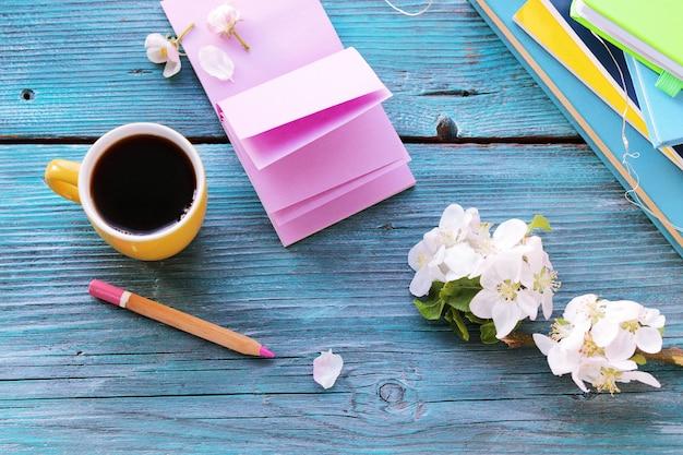 空白のノートと鉛筆、コーヒー、木製のテーブルの花、春を開く