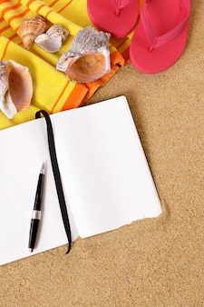 Open blank notebook on the beach