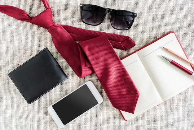 Open blank notebook, pen, pencil, smartphone, wallet, sunglasses on clean sackcloth with red necktie