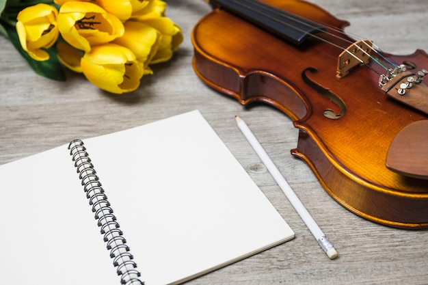 An open blank notebook; pencil; tulip and classical violin on plank backdrop