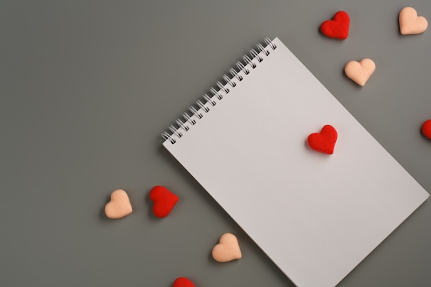 Open blank notebook, red heart on gray background. valentine's day and romantic holiday concept. love message. top view, flat lay with copy space.