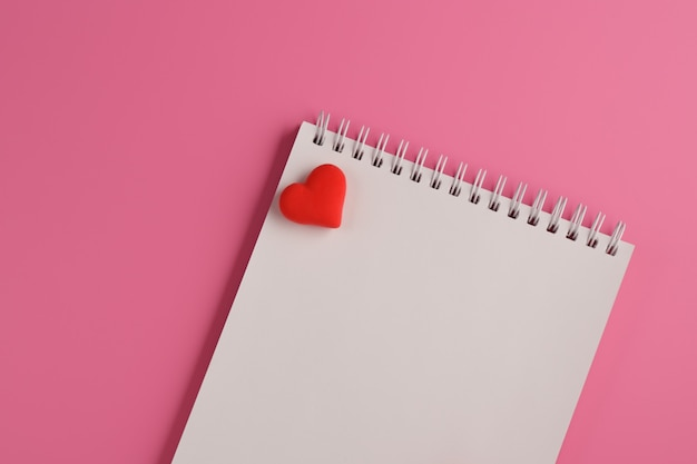 Open blank notebook, red heart on pink background. valentine's day and romantic holiday concept. love message. top view, flat lay with copy space.