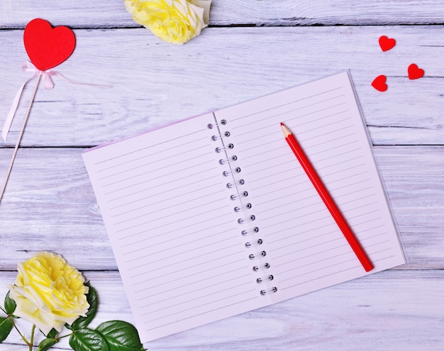 Open blank notebook and red wooden pencil