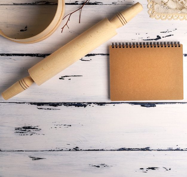 Open blank notebook with brown pages and a wooden rolling-pin with a round wooden sieve