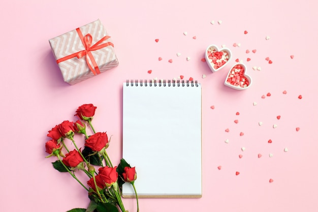 Open blank notebook with gift box, flowers and hearts on a pink background