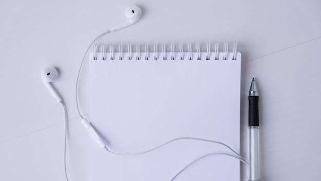 헤드폰과 검정 펜으로 빈 노트북을 엽니다. 공간 적 텍스트를 복사합니다. 평면도. 파스텔 색상