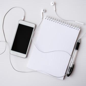 헤드폰 휴대 전화로 빈 노트북을 엽니다. 검은 화면과 검은 펜. 공간 적 텍스트를 복사합니다. 평면도. 파스텔 색상