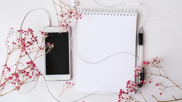 헤드폰 휴대 전화로 빈 노트북을 엽니다. 검은 화면과 검은 펜. 드라이 핑크 꽃 장식입니다. 직장. 공간 적 텍스트를 복사합니다. 평면도. 파스텔 색상